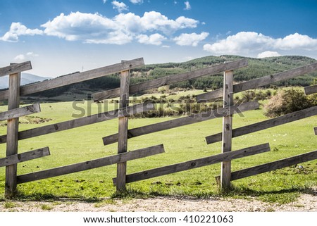 Wooden fence on a mountain ranch. Sunlight