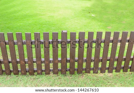 Wooden fence on grass background