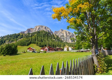 Wooden fence on green meadow with traditional alpine houses in distance in summer landscape of Dolomites Mountains, Italy - stock photo