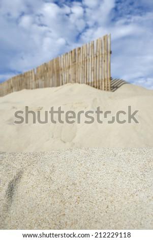 Wooden fence on sandy beach against cloudy sky - stock photo