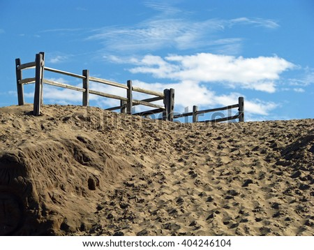 Wooden Fence on top Sand Dunes Against Blue Sky - stock photo