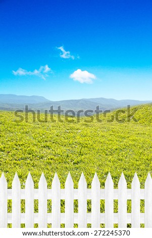 Wooden fence open grassland and sky. - stock photo