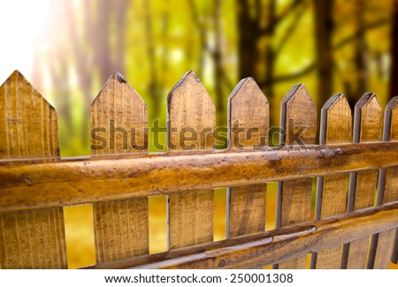 Wooden fence overlooking the autumn background - stock photo