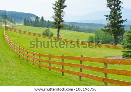 wooden fence with green field and rolled hay - stock photo