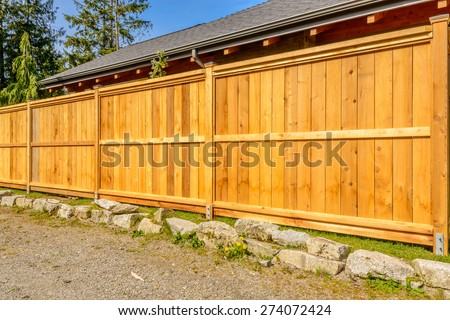 wooden fence with green lawn and houses - stock photo