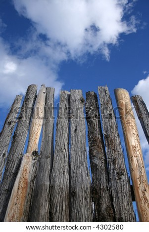 wooden fence with rough bark against sky background