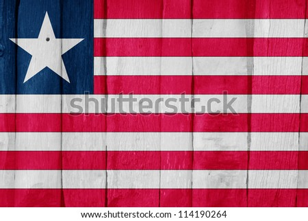 Wooden fence with the flag of Liberia painted on it - stock photo