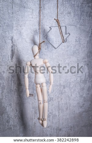 Wooden figure of human and house hanging in the hangmans loop - stock photo