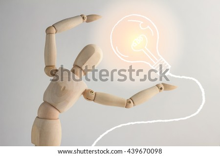 Wooden figure showing up drawing of bulb on white background  and copy space for your text creativity ideas concept - stock photo