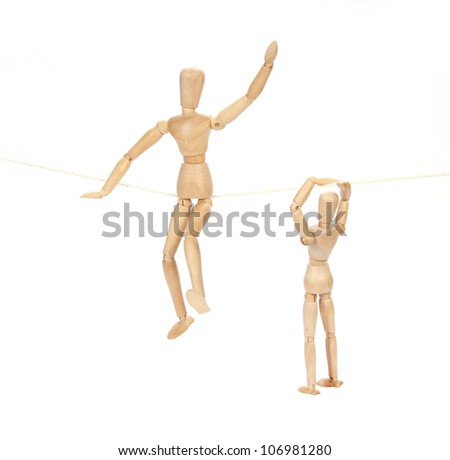 wooden figure sitting on rope concepts
