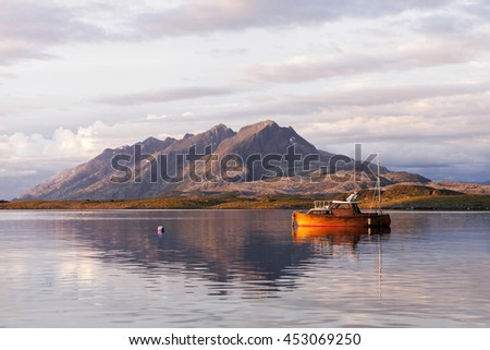 Wooden fishing boat at still sea in evening light, with mountain range at background. Photographed in Helgeland, Norway.  - stock photo