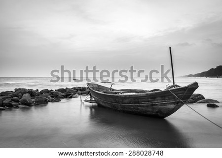 Wooden fishing boat on sea beach Thailand, black & white style - stock photo