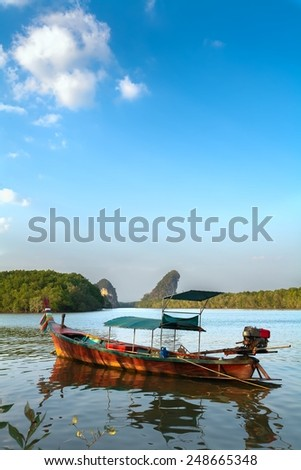 wooden fishing boat with motor on the lake in the evening - stock photo