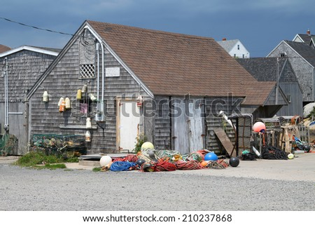 Wooden fishing shack with buoys hanging and colorful ropes in Peggy's Cove, Nova Scotia, Canada - stock photo