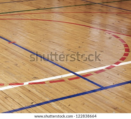Wooden floor of sports hall with colorful marking lines - stock photo