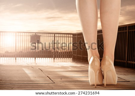 wooden floor of terrace with sunset of summer time and legs of woman on heels  - stock photo