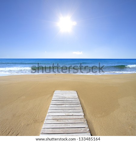 Wooden floor on golden sandy beach - stock photo