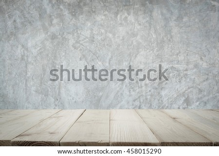 Wooden floor or wooden table with concrete wall for background.