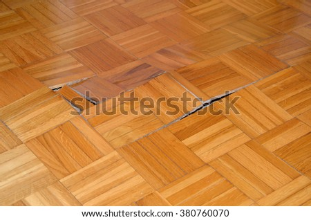 Wooden floor starts to lift up under influence of moisture or water. - stock photo