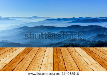 Wooden floor with morning mist mountains during sunrise ,Chiang Mai Thailand.  - stock photo