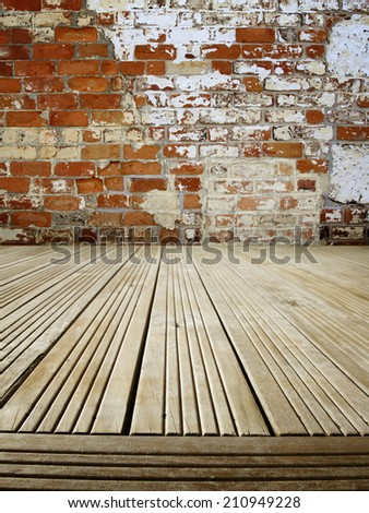 Wooden floorboards and brick wall - stock photo