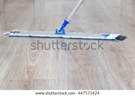 Wooden floors professional washing with mop in the room.  Regular clean up. Maid cleans house. - stock photo