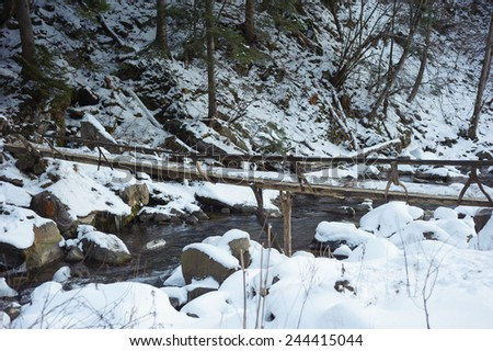 Wooden footbridge across stream in the winter mountain forest - stock photo