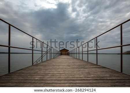 Wooden footbridge ending with a house on a cloudy day - stock photo