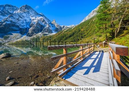 Wooden footbridge on path along Morskie Oko lake in autumn colours with fresh snow covered peaks, High Tatra Mountains, Poland - stock photo