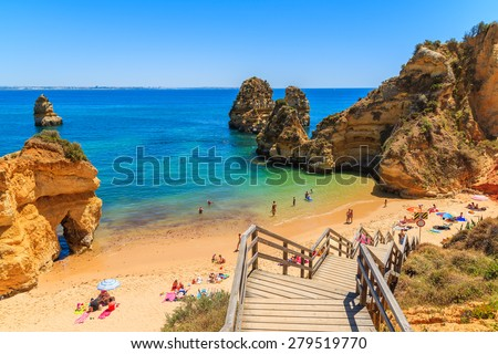 Wooden footbridge to beautiful beach Praia do Camilo, Portugal - stock photo