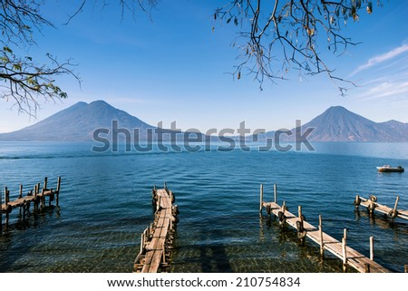 Wooden footbridges on the lake Atitlan in Guatemala with volcanoes on the background - stock photo