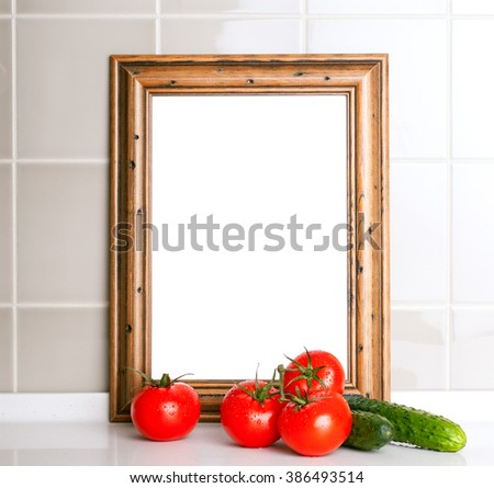 Wooden frame for the menu. Tomatoes and cucumbers in the foreground. Ceramic tile in the background - stock photo