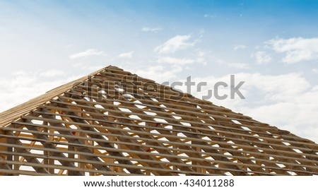 Wooden frame for the roof of the house on a background of blue sky