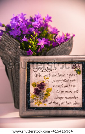 Wooden frame with Mothers greetings text with beautiful purple Campanula flowers behind , Happy Mother's Day