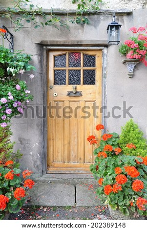 Wooden Front Door of a Beautiful Old English Cottage - stock photo