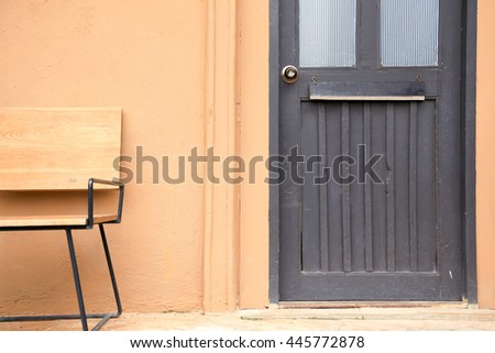 Wooden front door with a wood chair in orange wall of home