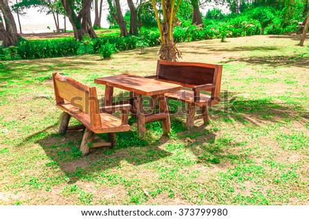 Wooden furniture table and chairs in the nature environment in summer. warm tone. - stock photo
