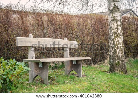 Wooden garden bench in the spring in the daytime - stock photo