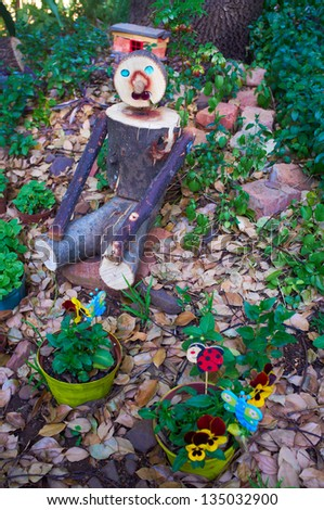 Wooden garden decoration. Man sitting between the violets and ferns