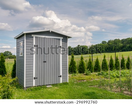 Wooden garden tools shed painted in gray color - stock photo