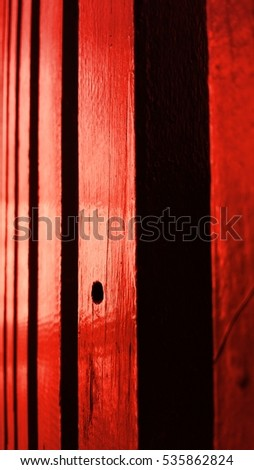 Wooden gate in the afternoon light. Red gate with a knothole.
