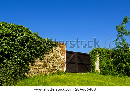 wooden gate in the middle of a wall of stone and brick overgrown with ivy - stock photo