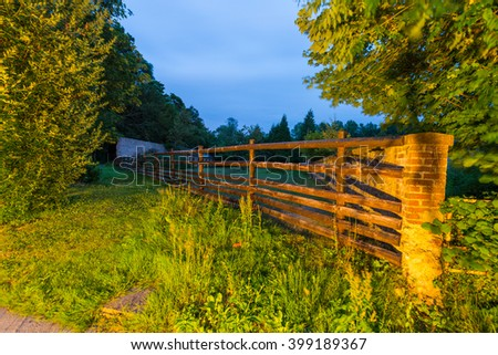 Wooden gate of a ranch at night.
