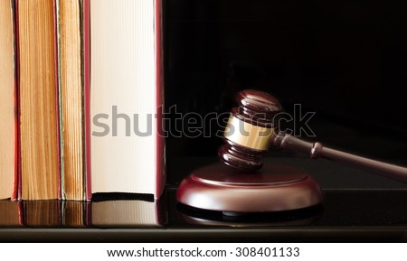 Wooden gavel and books on black background