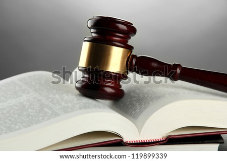 wooden gavel and books, on grey background
