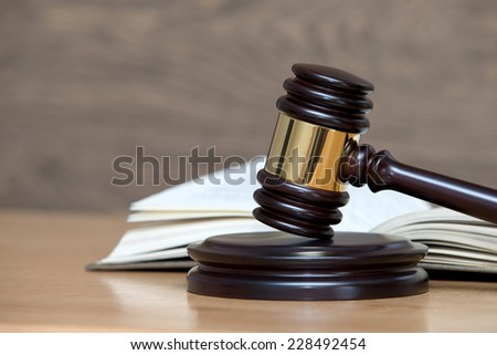 wooden gavel and books on wooden table - stock photo