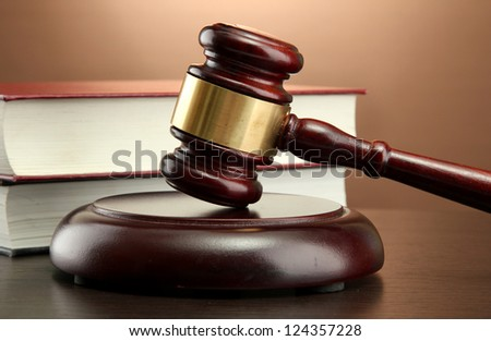 wooden gavel and books on wooden table, on brown background - stock photo
