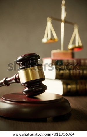 Wooden gavel and books on wooden table. Scale on books in background. - stock photo