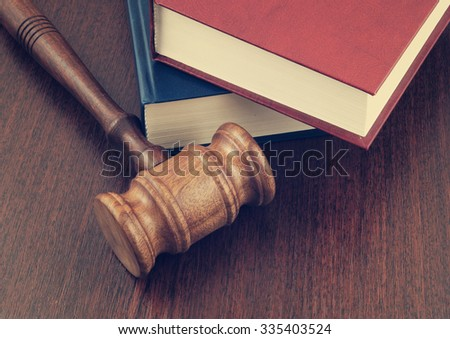 Wooden gavel and legal books on wooden table - stock photo