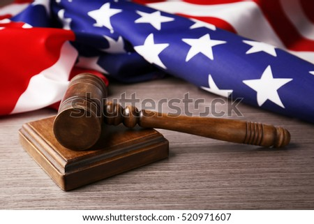 Wooden gavel and USA flag on table